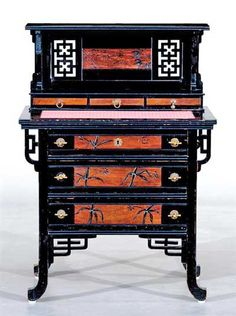 An ebonised Anglo-Japanese desk with marquetry and incised bamboo decorated drawer panels. Unknown make and manufacturer.