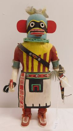 """41: Hopi Hochani Kachina, circa 1940s. Made of cottonwood, paint, feathers, leather and yarn, the item measures 5"""" x 3.25"""" x 11"""" tall. Hopi, Northern-Central Arizona. This kachina has a leather concho belt with quiver and arrows, holding a bow in left hand and a dance rattle in the other. Condition: Good, minor paint and feather loss, has dust, see images. Shipping: $25.50 w/insurance and signature, fragile item."""