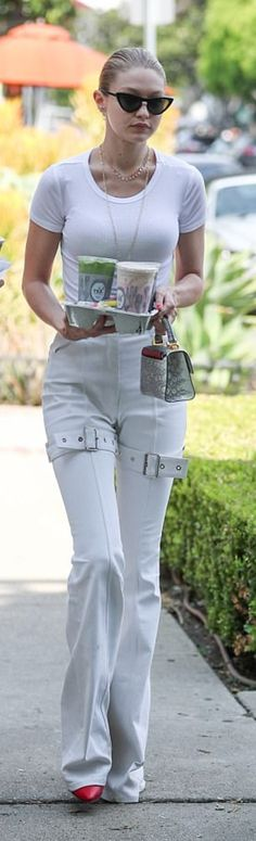 Who made Gigi Hadid's black sunglasses, white pants, red boots, purse, and Iphone case?