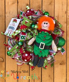 """This cute Christmas elf wreath is a fun fit for a Cute Christmas theme. This elf wreath is made up of red and green deco mesh and fun bright ribbons containing red green polka dots, a fun elf leg and hat print, a geometrical red and green print, and a red and green striped edge print! This elf wreath contains a cute elf doll wearing a red and green sequence suit with orange hair and a cute hat! The Cute Christmas wreath also has a fun sign saying """"This House Is Under Elf Surveillance"""""""