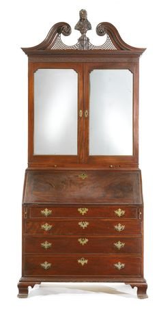 THE POTTS FAMILY CHIPPENDALE CARVED & HIGHLY FIGURED MAHOGANY SCROLL-TOP DESK-AND-BOOKCASE WITH BUST OF JOHN LOCKE, Philadelphia, Pennsylvania, Circa 1770 - Appears to retain its original finial bust of John Locke & brass casters. Rich brown color. Although always fitted with mirrored doors, the mirror plates may not be original. Height 115 1/2 in. by Width 42 3/4 in. by Depth 24in.