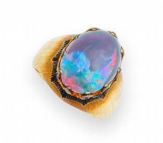 An opal, sapphire and ruby ring, Buccellati.  centering a black opal accentuated by a bezel of alternating circular-cut rubies and sapphires in a broad textured gold mount; signed Buccellati