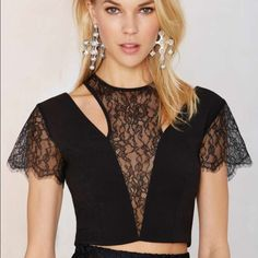 NWT Nasty Gal black lace crop top Nothin' but love for this one. The Crop Top is black and features sheer lace panels, cutout detail, scalloped edging at sleeves, and scoop neck. Fully lined, side zip and back button closures. Team it up with a mini skirt and chelsea boots, or skinnies and a chunky heels. By Nasty Gal.  *Polyester/Spandex/Nylon *Runs true to size *Machine wash cold Nasty Gal Tops Crop Tops