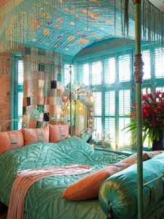 Lovely boho mint & coral colour mix on this four poster canopied bed.  Fabulous window wall.