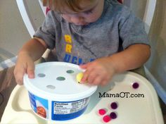 Push pom poms into holes in a plastic container for fine motor practice. This is just 1 of the 25 occupational therapist-approved  fine motor activities you can do with your child, using items from around your house!