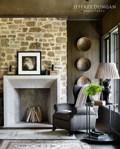 Magnificent living room with stone wall, fireplace, and wingchair. Traditional and classic decor. Farmhouse on Shades Creek. Farmhouse Fireplace, Fireplace Wall, Fireplace Surrounds, Fireplace Design, Fireplace Ideas, Fireplace Stone, Country Fireplace, Cottage Fireplace, Fireplace Cover