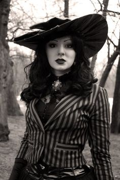 Gothic outfit with hat and striped jacket. She looks very classy while still being able to dress goth.