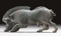 A GREEK BRONZE BOAR APPLIQUÉ   Archaic Period, Circa Early 5th Century B.C.   Depicted in high relief, in profile to the left, with a high ridge of bristles along its head and upper back, a rounded ridge along its hindquarters, its head lowered, the tusks protruding, the tail curled, the genitalia rendered