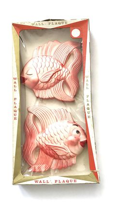 A fabulous vintage chalkware fish set circa 1954 by Miller Studio, Inc. This adorable pair of coral kissing fish come to you in there original box never used. Painted in a pearlized lighter darker shade of coral with a black eye and eye brow and vibrant red lips and lots of wonderful details. Signed 1954 Miller Studio Inc.   The fish are in excellent condition with the exception two tiny minor paint chips on one, which you can in a photo. The box is very 50s cool but does have wear…