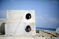 GAZA CITY: Palestinian children play on the beach near the Shati refugee camp in Gaza City on August 28, 2013. AFP PHOTO / MOHAMMED ABED