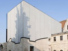 Music School Louviers Extension by Opus 5 - Prefabricated concrete panels follow the shape of the existing building below.