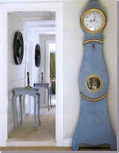 Antique clock in Carolina Blue! and love white wood hallway w/ matching tables with candlesticks. Yes, please.