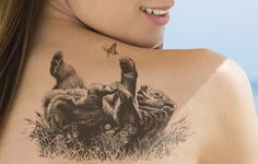 Tattoo of a playful black bear on back
