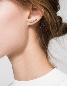 A handcrafted pair of mismatching earrings, one with a small turquoise and small diamond pendent, one with a five-turquoise arc design with a triangle end from Loren Stewart. • Handcrafted pair of mismatching turquoise earrings • Straight back post wi