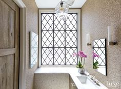 A granite-like wallcovering by Phillip Jeffries adds dimension to the guest bathroom. A handblown glass pendant by John Pomp, from R Hughes, reminded the designer of jellyfish. The sink and faucet are from The Fixture Exchange.