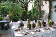 Garden dinner party... could put trees behind each table to give it this feel? also, love the number of simple centerpieces on the tables.... i would have with flowers instead
