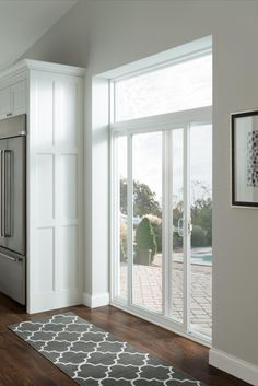 This patio door, with a transom above, allows light to flood this kitchen while the screen lets you enjoy fresh air anytime. Don't stop at the door, take advantage of the space surrounding the door with additional windows. Hinged Patio Doors, Sliding Patio Doors, Sliding Glass Door, Sliding Door Curtains, Glass Doors, Wood Doors, Transom Windows, Windows And Doors, Sliding Door Window Treatments