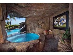 Outdoor pool connected to partial indoor jacuzzi with wall big-screen TV