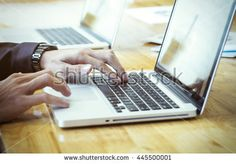 Businessman's hands typing on laptop keyboard