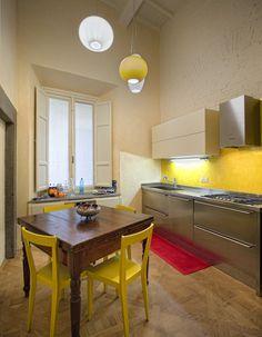 Cucina in acciaio Mittel, sedie gialle di L'Abbate, lampade Foscarini
