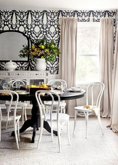 Wallpaper looks especially striking behind the simple silhouettes of a dining-room table and chairs.