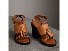 A pair of leather sandals inspired by the tasselled penny loafer. A wraparound strap frames the ankle, and the style is balanced with a block heel.