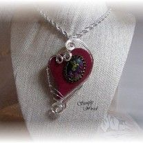 A dyed ruby heart shaped agate adorned with a hand painted cameo and wire sculpted in silver filled wire.  SOLD