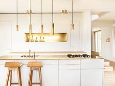 Kitchen: white handleless cabinets; gold benchtop, splashback, tapware and pendant lights