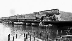 New York Central 4-6-4 Hudson streamlined steam locomotive # 5449, is seen hauling the 20th Century Limited across a mainline bridge at Peekskill, New York, 1941