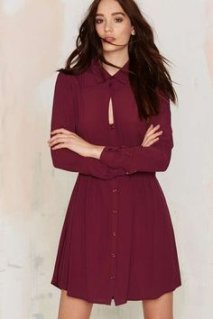 The Keyhole In One Dress comes in burgundy and features collared button up design, banded waist, button closure at front and cuffs, and mini dress silhouette.