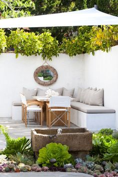 Great use for the garden wall. Built-in seating with pillows, a dining table, and canopy shades this lounge area well.