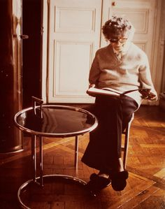 Eileen Gray in her later years, sitting beside her famous adjustable table.