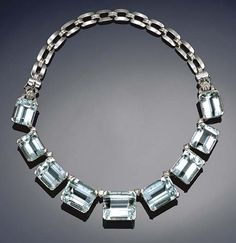 An impressive Art Deco aquamarine and diamond necklace the front composed of a series of nine graduated rectangular step-cut aquamarines with brilliant-cut diamond single stone links between, on a back chain of pieced buckle shaped links with diamond set stirrup connections to either side, circa 1940, length approximately 40.5cm.