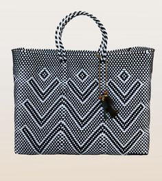 """- Crafted of black and white recycled plastic woven in geometric pattern. - Short straps 4"""" approximately. - Measures: 13"""" height, 16"""" width approximately. - Open top - Handmade in Oaxaca"""