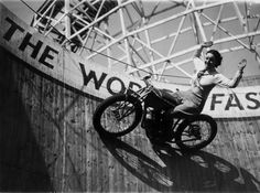 "Marjorie Dare (Doris Smith) riding hands free around ""The Wall of Death"" sideshow at the Kursaal amusement park in Essex, England, 1938."