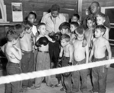 Nine-year-old John Mefford blows a bubble while coach Leonard Hawkins laces his glove for a bout with Dennis Miller. Hawkins and Paul Jefferson opened a junior boxing organization at the City Mission Gym in Omaha in the fall of 1956. THE WORLD-HERALD
