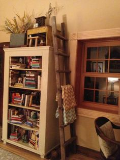love this look. bookcase, blanket ladder, and primitive decor on top