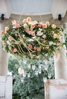 This classic floral chandelier, created by Kim Starr Wise, is filled with peach-and-pink roses. Hanging candles are suspended below for an extra dash of romance.