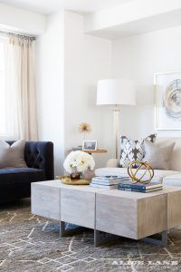 A family room abounding in natural warmth with a wood coffee table, blue tufted side chair, and nature inspired art. It's all about style and comfort in this space. Solameer Townhouse, Designed by Alice Lane
