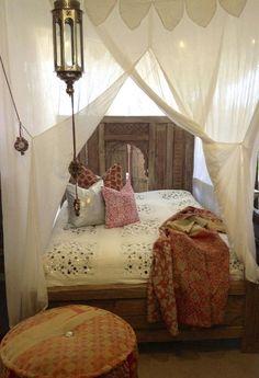 chambre adulte bohème avec un drap de lit blanc décoré de cristaux brodés, coussins décoratifs et ciel de lit semi-transparent