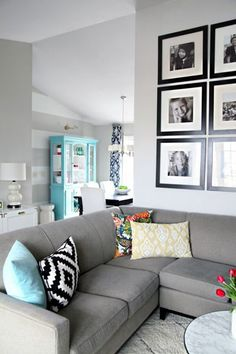 ideas for how to style a couch with toss cushions. Living room decorating and decor with gray walls and art gallery