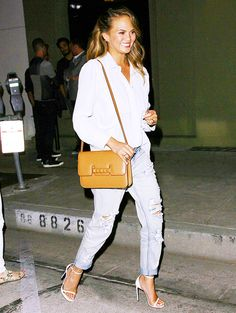Chrissy Teigen wearing ripped boyfriend jeans with a white button-up shirt and a leather camel cross-body bag