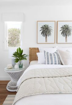 Coastal bedroom with palm tree art via @donna_guyler_design - rattan headboard, a wicker nightstand and two matching palm tree artworks above the bed