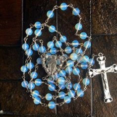Moonstone beads and refract highlight this beautiful wrapped loop rosary. Center piece is of the holy mother and Holy Child surrounded with a heart of roses. The crucifix is accented with hearts. Both the center piece and crucifix are made of pewter