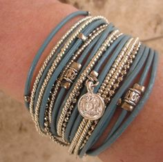 """Boho chic,turquoise leather wrap bracelet is made with 4 cords of leather. I have added silver tone crimp beads, tibetan beads and charms. This particular bracelet has a pomegranate, kabbalah symbol """"ELAD"""" for health, jewish star and spiral."""