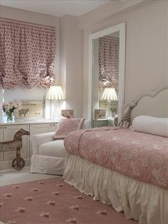 Pink and white nursery with a daybed (for mom) with an upholstered headboard and paisley printed duvet and a wooden rocking horse