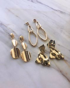 Beautiful shapes and textures in gold. From left to right: Caressa Drop Earrings, Aphrodite Earrings and Lilja Lava Earrings. See more at www.thehexad.com #goldearrings #marbletable