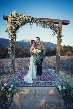 Burlap and an Oriental Rug over our railroad tie altar platform, with huge beams to make our arch, gorgeous floral arrangements, surrounded by mountains, grass, sky, sunset, burlap and flower petals :)