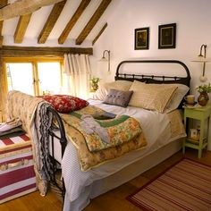 I love this cozy bedroom with the natural light and exposed rafters. Love the country feel of a metal bed frame and lots of mis-matched quilts