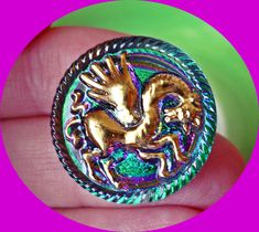 Super iridescent Czech glass button with a golden Pegasus #button #buttons #czechglassbuttons #glass #czechglass #golden #iridescent #Pegasus #mythical #colourful #gold #green #purple